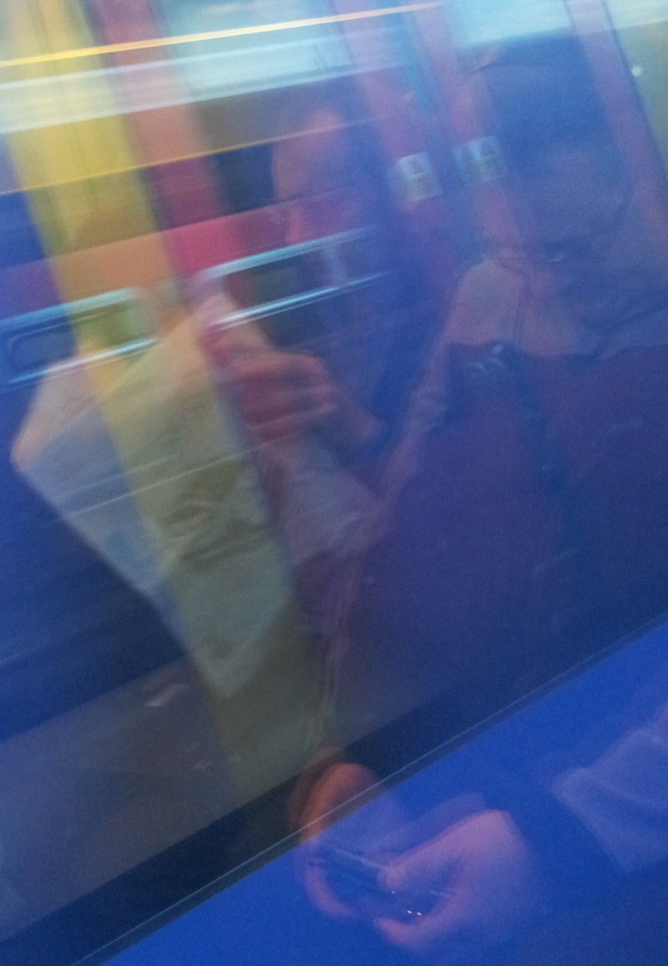 A serendipitous shot with the phone. Two passengers reflected in the window of a train, turned into a mirror by a passing carriage.