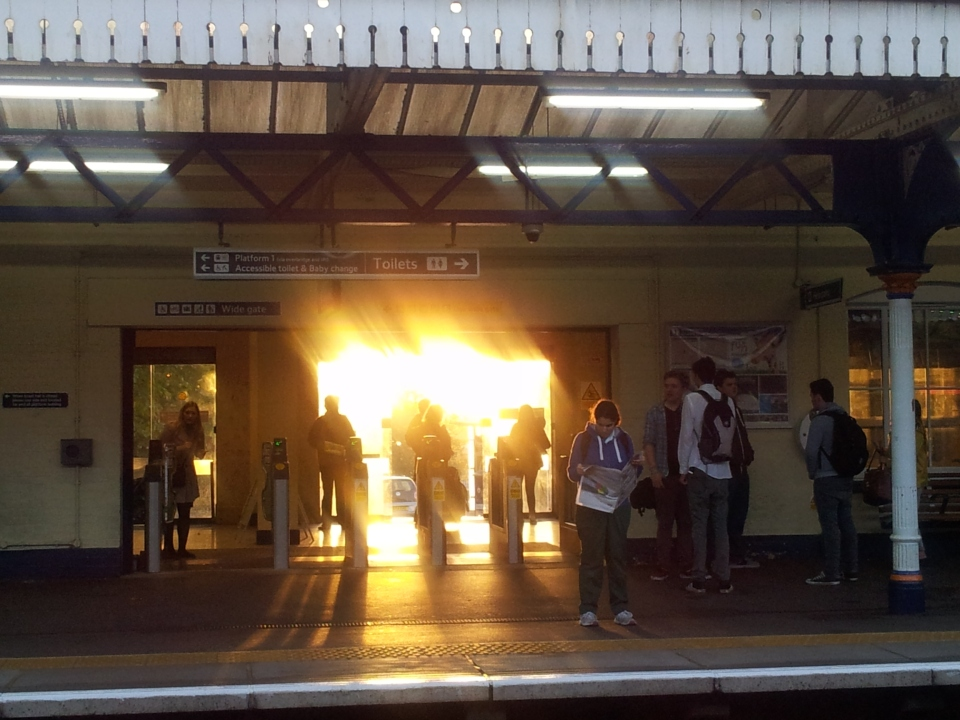 The sun rises directly behind the main entrance to Winchester station